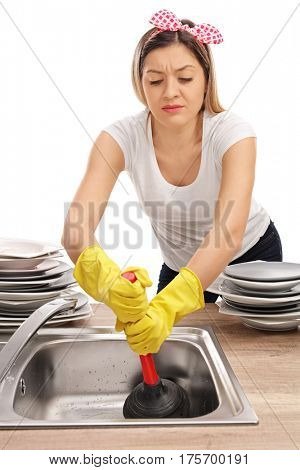 Young woman using a plunger to unclog a sink isolated on white background