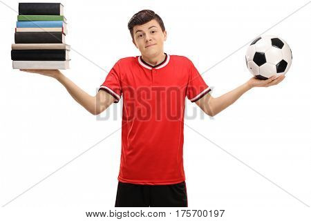 Indecisive teenage boy holding a stack of books and a football isolated on white background