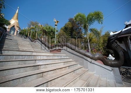 UDON THANI,THAILAND - JAN 25,2014:The Chedi Prathom Rattanamahaburaphachan above the steep staircase.The Chedi in Sri Lanka style, richly adorned with small golden mosaic stones,marble and granite ,in Wat Pa Phu Kon of Ban Na Kham,Na yung District in Udon