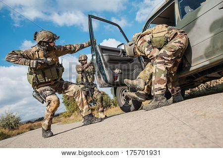 Squad of elite french paratroopers of 1st Marine Infantry Parachute Regiment RPIMA detaining terrorist in the car, low angle view poster