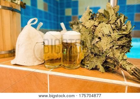 Bath accessories in the Russian bath. Bathroom items of traditional Russian sauna. two mugs of light beer, bathing caps, bath brooms from oak leaves against the background of the pool.
