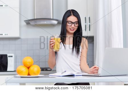 Brunette girl in glasses studying, writing home task at kitchen and using lap top. Morning of student and successfully people. Near on table books, glass of juice and plate with oranges.