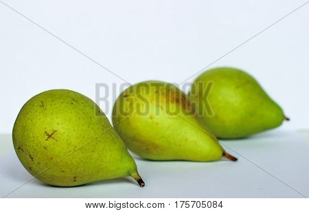 three pear lie next to, three pears on white background, green pears, the fruits are arranged in a row, three pears