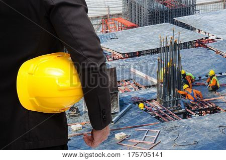 double exposure of businessman hold in hand yellow safety helmet  industrial concept on construction site workers background.