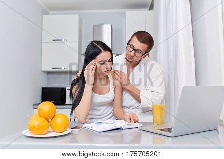 Portrait of tired brunette woman reading and studding at kitchen in morning. Boyfriend in robe holding hands on shoulder her girlfriend caring and helping with study. Laptop and fruits near on table