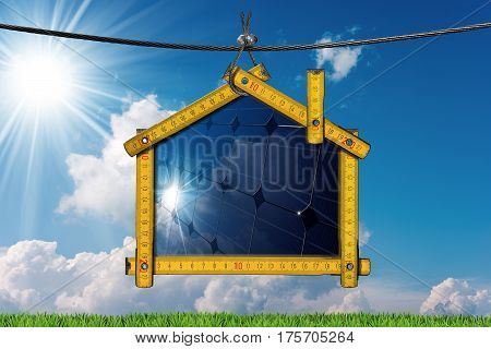 Wooden ruler in the shape of a house hanging on a steel cable with a solar panel inside. Concept of ecological house project