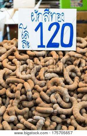 Group of ripe tamarind pods on the table with price card