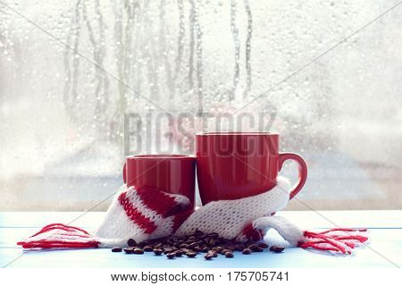 Two red mugs in a scarf stand on a table in the background of a window with dripping rain drops / cozy aroma of coffee