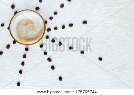 glass mug with a frothy cappuccino and coffee beans on the table / hot sunny drink