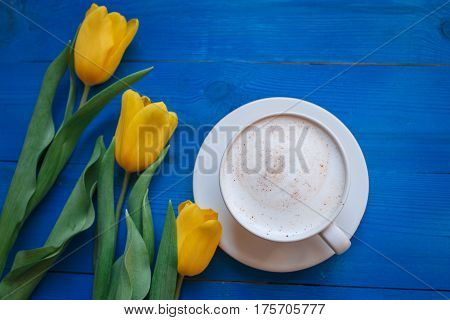 Coffee mug with yellow tulip flowers and notes good morning on blue rustic table from above, breakfast on Mothers day or Womens day .Spring  flowers bouquet