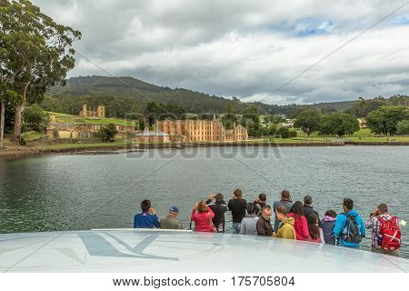 Port Arthur Histic Site, Tasmania, Australia - January 15, 2015: Group of tourists watch  from the boat after the trip to the Island of dead close to the main site