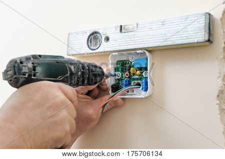 Installing a programmable room thermostat. Man's hands attach device to the wall using a screwdriver and spirit level.