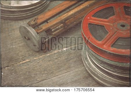 Reels with a film and an old wooden tripod lie on a table