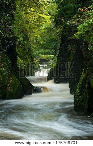 Flowing River Through Fairy Glen In Autumn
