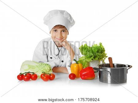 Cute boy in chef uniform with vegetables and saucepan on white background