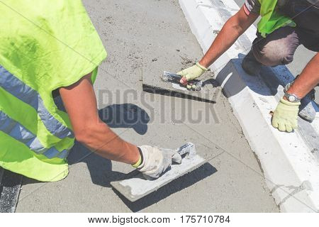 Construction workers working hard leveling concrete pavement outdoors.