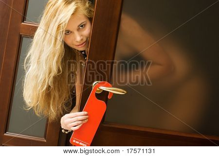 Pretty blond hanging do not disturb sign on door knob