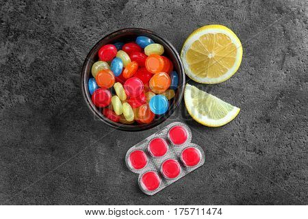 Different cough drops with lemon on grey background