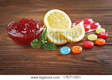 Cough drops with jam and lemon on wooden background