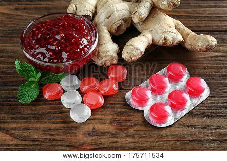 Cough drops with jam and ginger on wooden background