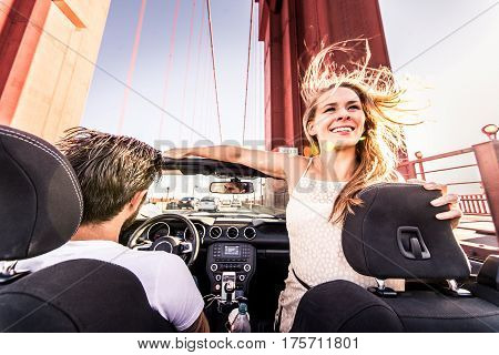 Couple of lovers driving on a convertible car - Newlywed pair on a romantic date woman with outstretched arms on Golden Gate Bridge