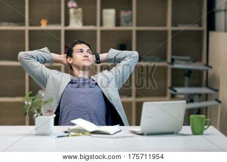 Young Man in casual Jacket sitting at grey working Place with Computer Flower Papers and Tea Mug relaxed Posture smiling thinking pensive Face expression on wooden Wall Background.