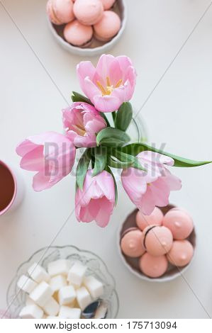 Spring background. Pink cake, lump sugar, a cup of tea and a bouquet of pink tulips on a white table, top view. Still life with fresh bouquet of tulips. Beautifully decorated tray.