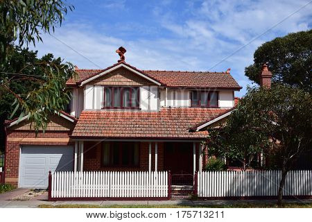 suburban house with red tiled roof and white picket fence on sunny day