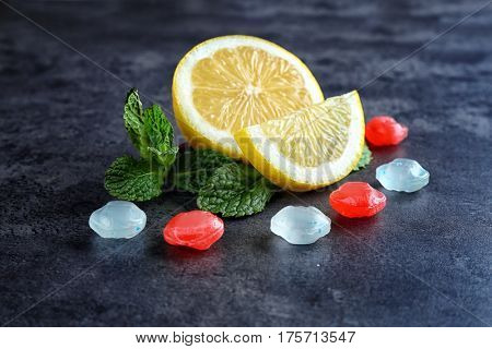 Cough drops with lemon and mint on color background