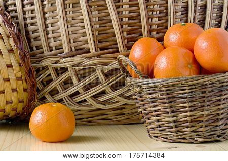 one whole tangerine and a wicker basket of tangerines on a background of a wicker basket on a wooden table