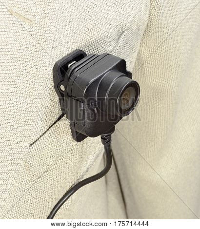 lens from the camcorder security police body camera with power cord in black color on a white suit jacket vertical from the top