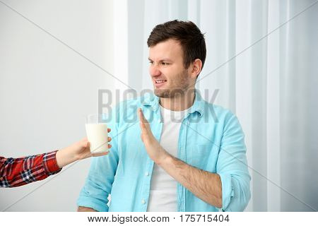 Young man with allergy refusing drink milk