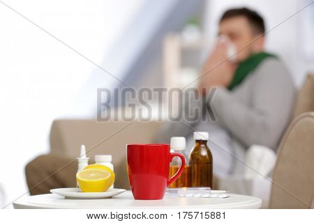 Cup of hot tea, lemons and medicines with blurred ill man on background