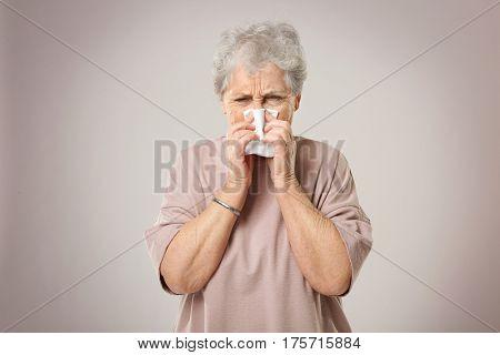 Portrait of elderly woman sneezing in handkerchief on grey background