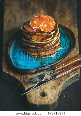 Homemade pancakes with honey and bloody orange slices for breakfast on blue ceramic plate over rustic wooden board, dark wooden scorched background, selective focus, vertical composition