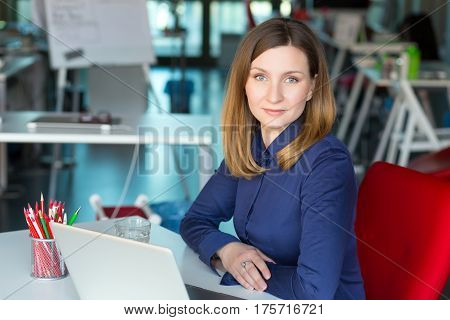 Smiling charismatic Business Lady in smart casual clothing Shirt sitting at grey Table with Computer and other Gadgets in contemporary digital corporate Office with large Window on Background.