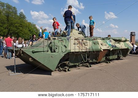 Kiev Ukraine - May 09 2016: Children are playing on a damaged armored personnel carrier delivered from the territory of an anti-terrorist operation and installed in a museum of the Second World War