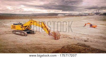 Working excavators in the clay open cast mine. Panoramic view of devastated industrial landscape.