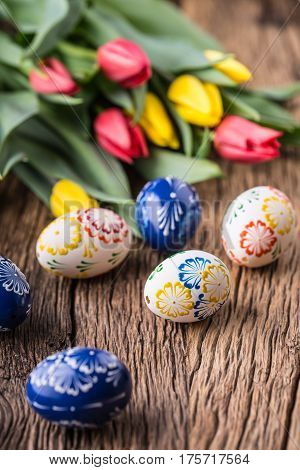 Easter. Hand made easter eggs and spring tulips on old wooden table.