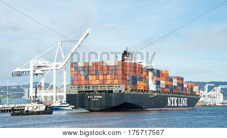 Oakland CA - March 07 2017: Tugboat MICHELLE SLOAN off the stern of Cargo ship NYK ATHENA assisting the vessel to maneuver into the Port of Oakland.