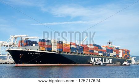 Oakland CA - March 07 2017: Cargo ship NYK ATHENA entering the Port of Oakland the fifth busiest port in the United States.