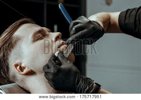 BARBERSHOP THEME. BARBER IN BLACK RUBBER GLOVES IS TRIMMING THE BEARD OF HIS YOUNG HANDSOME CLIENT WITH CLOSED EYES. HE IS USING A  STRAIGHT RAZOR