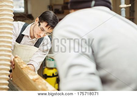 Two men holding timber on woodworking machine. Workplace equipped sleeves for hood. Rounded templates hanging on wall near machine-tool.
