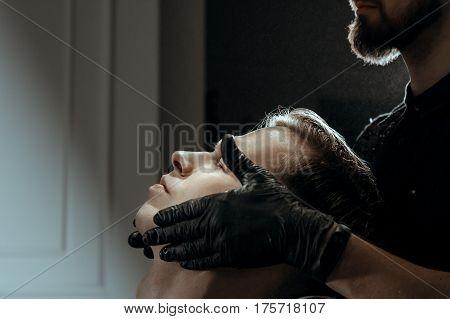 BARBERSHOP THEME. BEARDED BARBER IN BLACK RUBBER GLOVES  APPLIES AFTER SHAVING GEL ON CLIENT'S SKIN