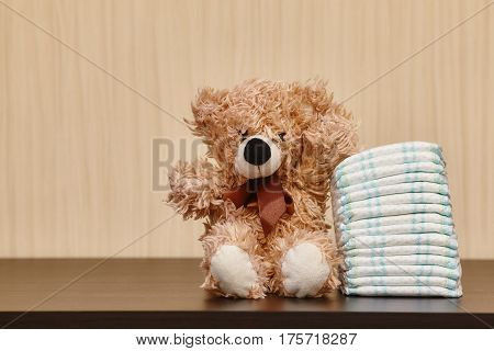 Stack of diapers or nappies with teddy bear closeup