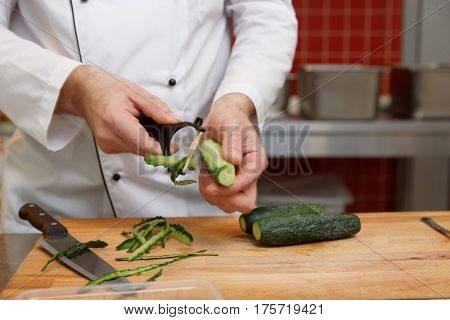 Chef is peeling cucumbers in restaurant kitchen, copy space
