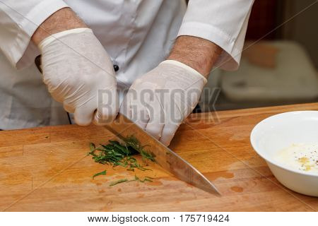 Chef is cutting herbs, professional cooking, routine kitchen operation