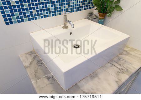 Bathroom interior with white sink and faucet.