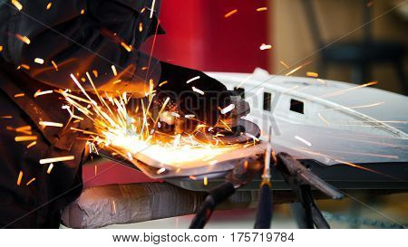 Professional car service - worker grinding metal construction with a circular saw, close up, telephoto