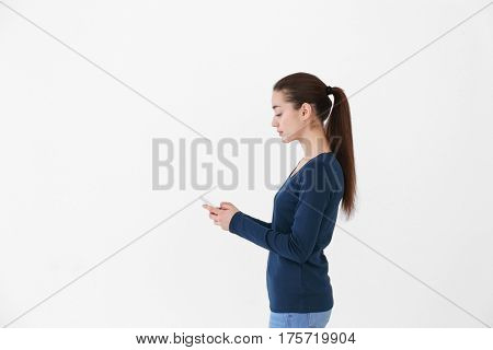 Posture concept. Young woman using smartphone against white background